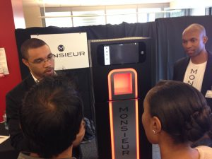 (File photo) Barry Givens, left, co-founder and Monsieur CEO, explains Monsieur's technology at an Atlanta technology and startup expo in September 2014.