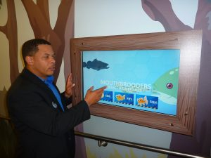 Brian Davis, the Georgia Aquarium's vice president of education and training, explains the interactive features of its Aquanaut Adventure exhibit, which features the technology of Merlin Mobility, an ATDC Select Company.